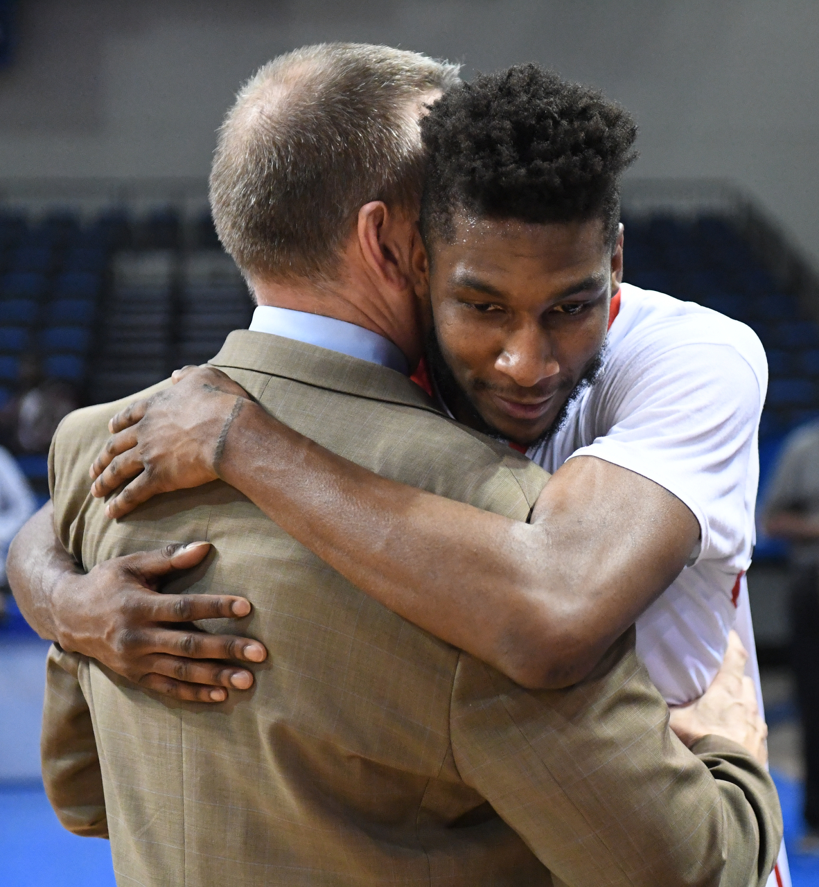 Basketball player his hugging coach